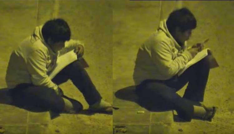 niño hace tarea en la calle con luz de poste